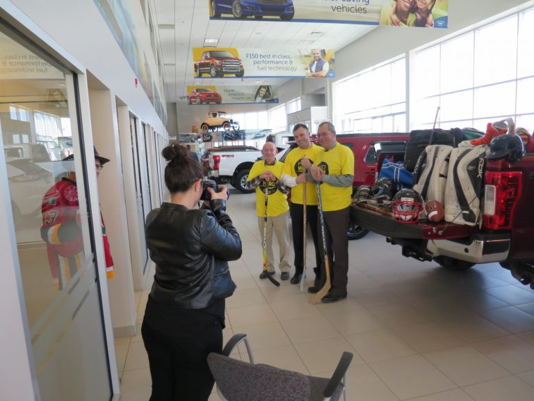 Ashton takes the photo of (L to R): Bearcat Murray (ex-Flames trainer), Rory Wood (General Sales Manager) and Rick Cherrington (General Manager)